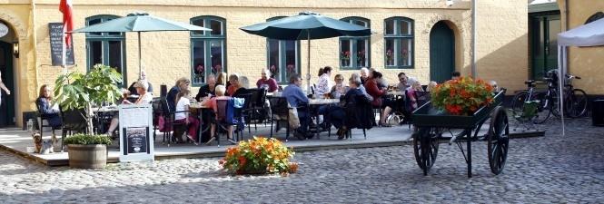 En fyldt terasse på Café CupCake set fra PLUMS GÅRD